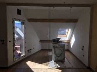 Porta corredissa de vidre muntada amb una guia d'alumini que pot anar subjectada a la paret o al sostre. Permet portar tapa per ocultar el mecanisme No porta cap guia al terra per a més comoditat.